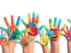 Mani di bambini colorate con sorrisi disegnati