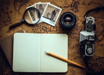 Macchina fotografica, quaderno, matita